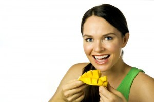 Young happy woman eating mango over white